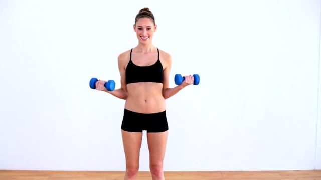 zadowolona kobieta ćwiczenia z hantlami - biustonosz sportowy filmów i materiałów b-roll