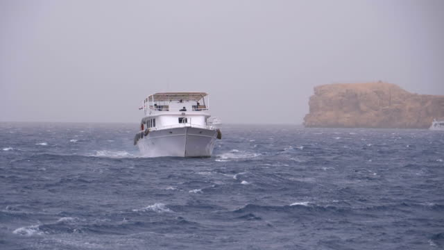 Pleasure Boat with Tourists is Sailing in the Storm Sea on background of Rocks. Egypt