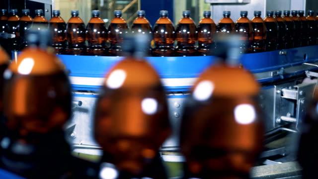 massor av ölflaskor rör sig längs den industriella transportör - biltransporttrailer bildbanksvideor och videomaterial från bakom kulisserna