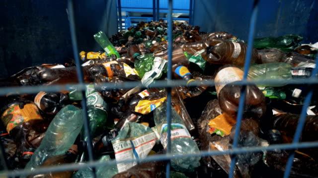 massor av begagnade plast flaskor inlagrade bakom barerna. - pet bottles bildbanksvideor och videomaterial från bakom kulisserna