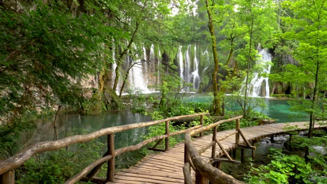 Plitvice Lakes National Park, Croatia, Europe. Walking on boardwalk in Plitvice lakes with turquoise water, waterfalls and green trees. Gimbal shot, 4K