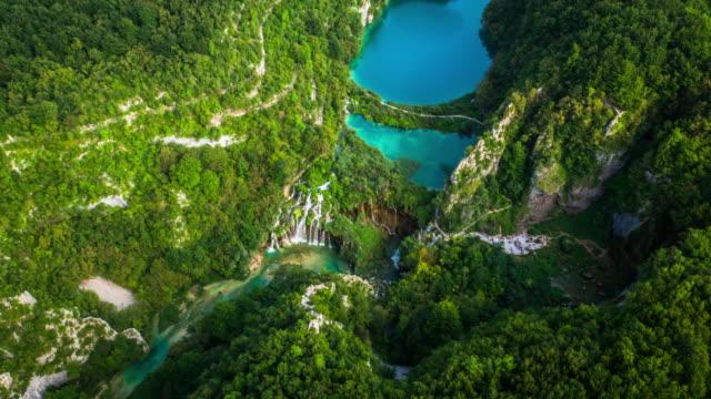aerial: plitvice lakes with waterfalls and surrounding forest - национальный парк плитвицкие озёра стоковые видео и кадры b-roll
