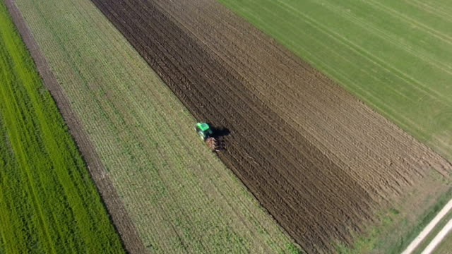 Plow Turning Over the Soil Aerial Flyover Shot