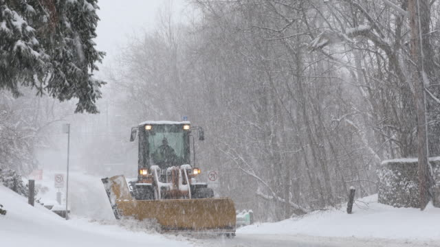 Plows clear a snow covered road Clearing the street in a winter blizzard storm plow stock videos & royalty-free footage