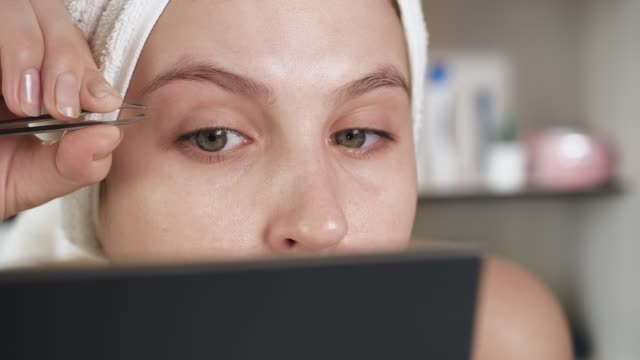 vídeos de stock e filmes b-roll de plucking eyebrows. girl with white towel on her head in bathroom looks in mirror and plucks her eyebrow hair with tweezers. hygiene, beautician, makeup, face care concept. close-up - sobrancelha