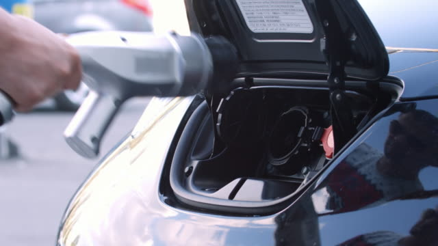 Plug in charging cord in electric car socket video