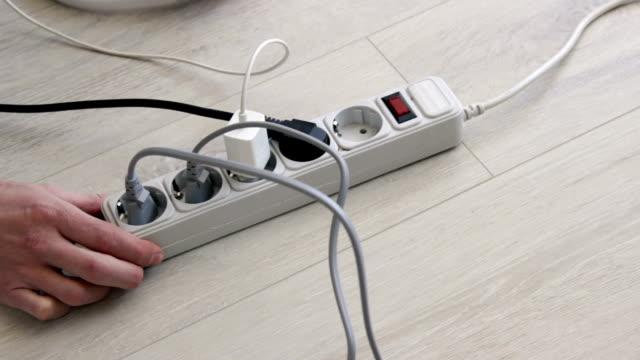 vidéos et rushes de brancher et débrancher un cordon d'alimentation à partir de protecteur de surtension . bande de tête. - vidéos de rallonge électrique