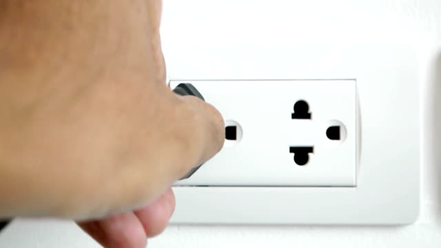 plugging and unplugging electronic into electric wall socket.
