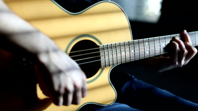 Plugging in the guitar Practicing acoustic guitar side lit stock videos & royalty-free footage