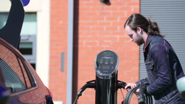 plugging into car charging station - carica elettricità video stock e b–roll