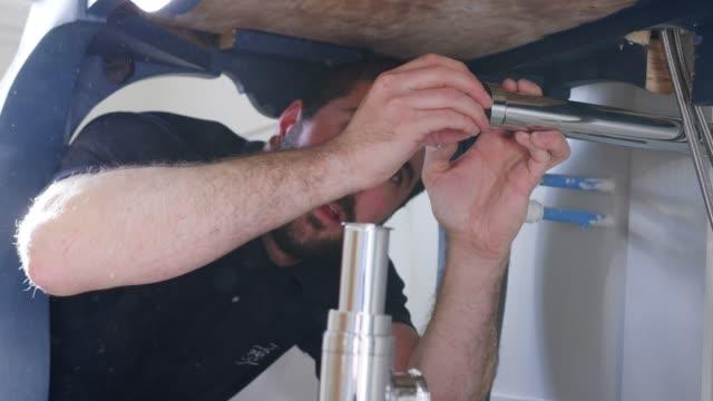 vídeos y material grabado en eventos de stock de plomero instalación nueva basura trampa para lavabo en baño - fontanero