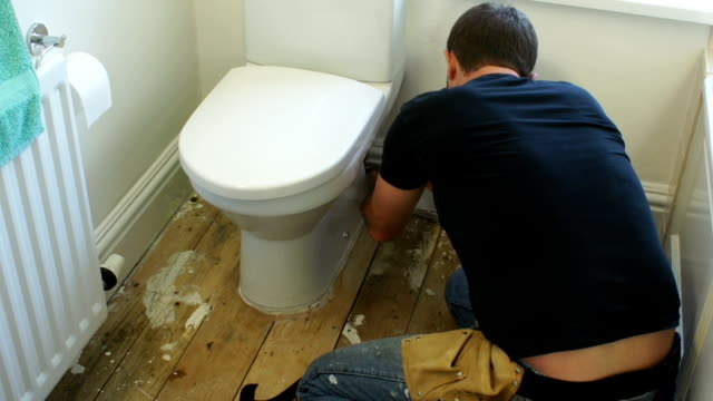 Plumber fixing a Toilet in the Bathroom video