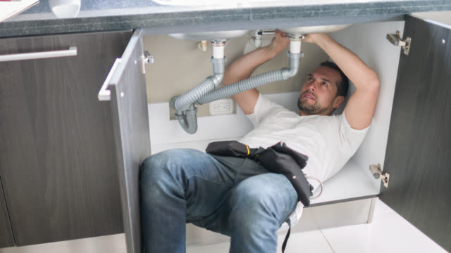 Plumber fixing pipes at a house
