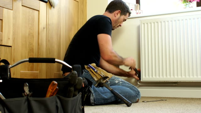 stockvideo's en b-roll-footage met dolly hd - plumber fixing radiator in house - gefabriceerd object