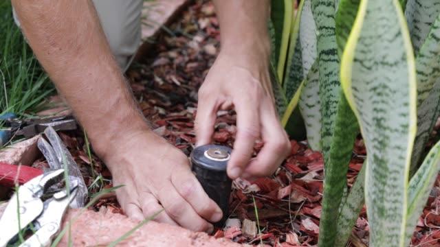 Plumber Man fixing Sprinkler Head in backyard Grass Field Sprinklers Installation by Professional Caucasian Garden Systems Installator. Adjusting Lawn Sprinkler. watering stock videos & royalty-free footage