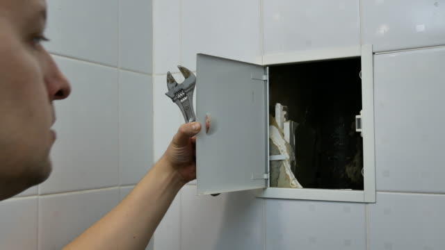 vídeos de stock e filmes b-roll de plumber man inspecting pipeline at home - obras em casa janelas