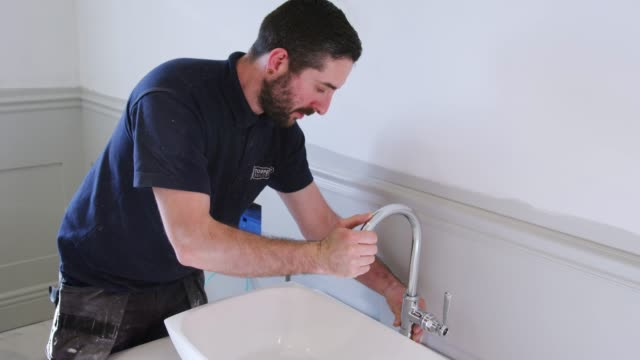Plumber Positioning Basin Taps In New Bathroom