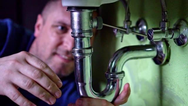 Plumber repairing a siphon