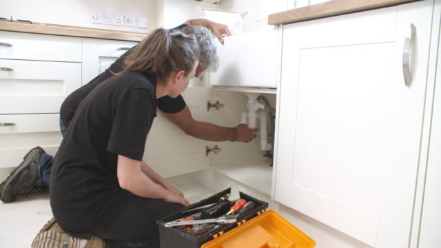 Plumber showing female apprentice how to fit a kitchen sink video