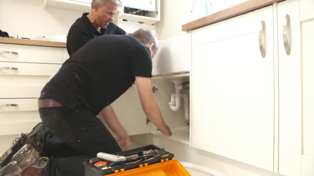Plumber teaching apprentice to fix kitchen sink video