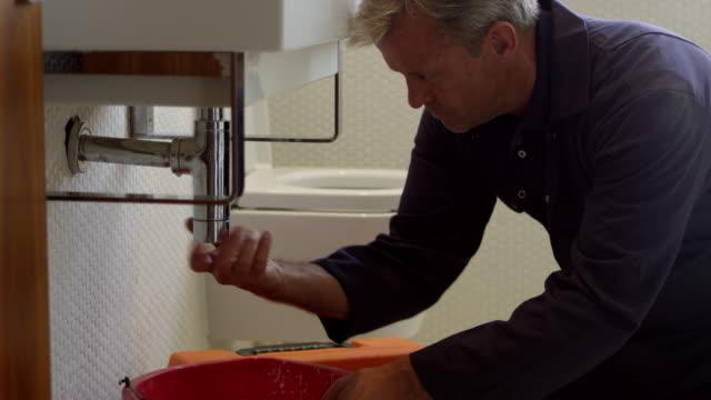 Plumber Working On Sink In Bathroom Shot On R3D – Video