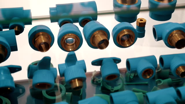 Plumbing parts - plastic with pressed brass thread, for sale at a shop window video