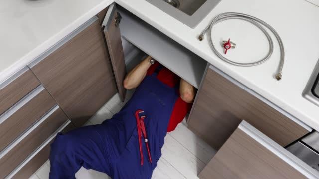 vidéos et rushes de services de plomberie - plombier travaillant dans la cuisine domestique, réparant des tuyaux d'évier - uniforme