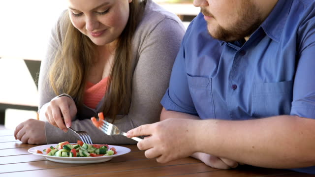 Plump couple eating fresh salad from one plate, weight loss, calories control Plump couple eating fresh salad from one plate, weight loss, calories control fat nutrient stock videos & royalty-free footage