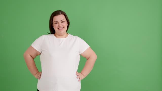 stockvideo's en b-roll-footage met mollig meisje glimlachend op het groene scherm - t shirt