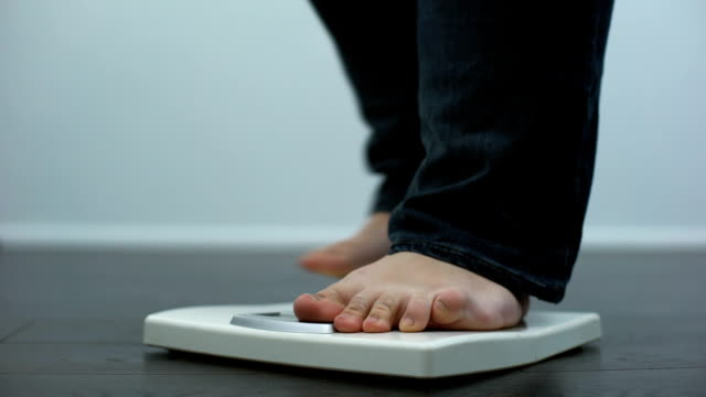 plump male checking body weight on scales, health disorder, overeating result - sovrappeso video stock e b–roll