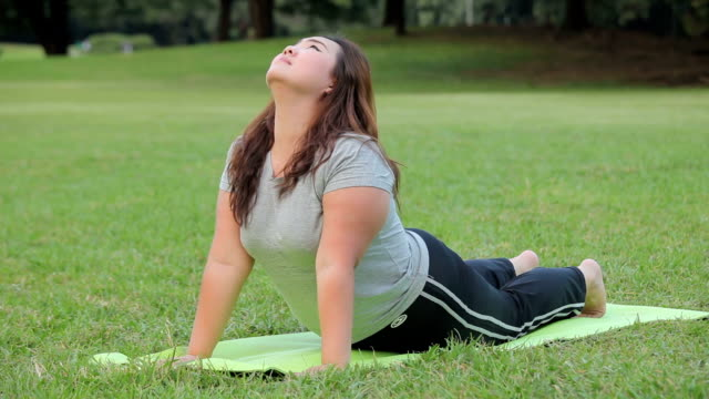 Plus size asian woman practicing yoga on green grass in the park video