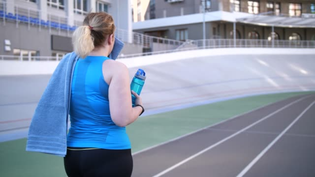 plus size female walking along track after running - body positive video stock e b–roll