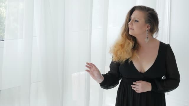 vidéos et rushes de modèle de taille plus dans la robe noire - décolleté