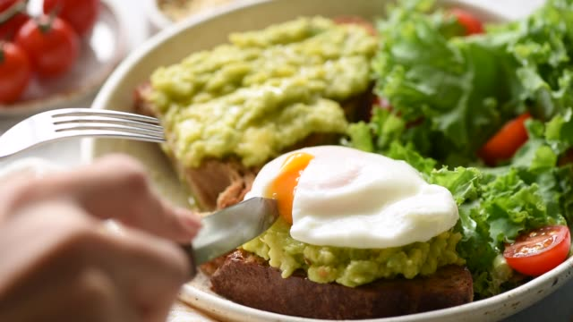 Poached egg on rye bread toast with avocado Poached egg on rye bread toast with avocado and green leaf salad kale. Healthy food, clean eating concept. Closeup avocado stock videos & royalty-free footage