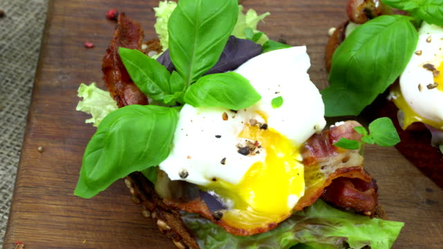 Poached eggs, lettuce and bacon on toasted bread. video
