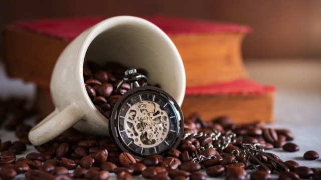 Pocket watch and coffee cup on coffee seed and old book on wooden table.