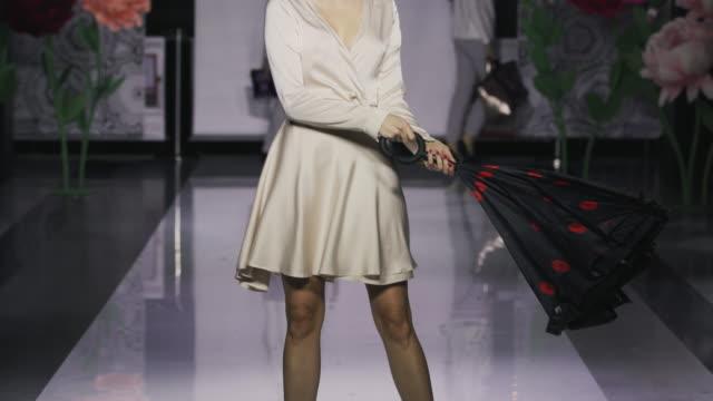 Podium charming woman open umbrella catwalk model show closeup evening vogue 4K.