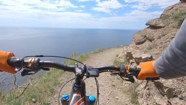 Point chest view from action camera bicycle handlebar and hands while riding on cliff edge trail along sea. Bicyclist holding handle wheel while riding on rocky mountain route on enduro mtb bike Point chest view from action camera bicycle handlebar and hands while riding on cliff edge trail along sea. Bicyclist holding handle wheel while riding on rocky mountain route on enduro mtb bike handlebar stock videos & royalty-free footage