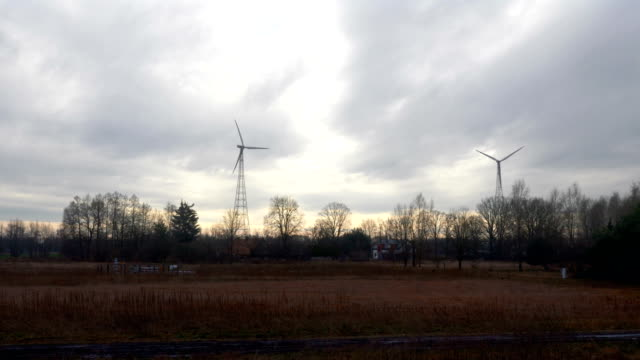 Point of view from train passing windmills at sunset in slow motion in 4k video