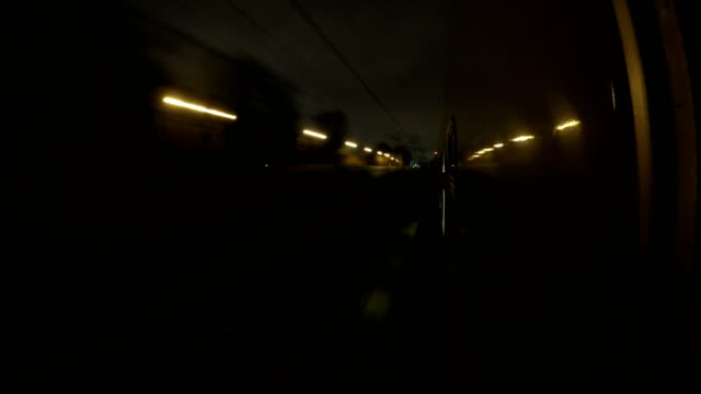 Point of view night train rushes by rail arrives and departs from platform, timelapse, night lights reflected in windows of train video