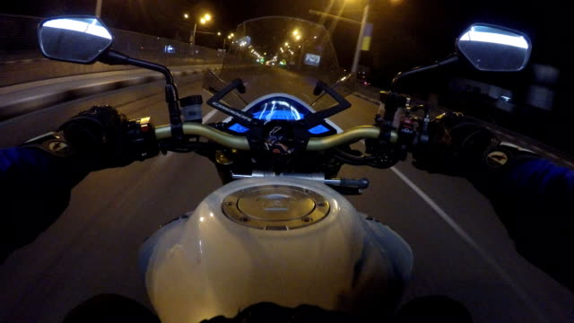 point of view of a motorcycle rider rides in evening town road in high speed. the viewpoint of motorcyclist driving in the night empty city streets. pov close up - motocross video stock e b–roll