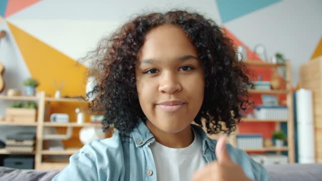 standpunkt der afro-amerikanischen mädchen, die selfie lächelnd blick auf die kamera zu hause - selfie stock-videos und b-roll-filmmaterial