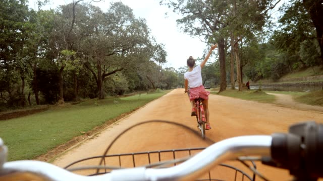 POV point of view of couple on bicycle enjoying sightseeing in Sri Lanka, man personal perspective cycling thing girlfriend in the jungle, couple having fun travel vacations