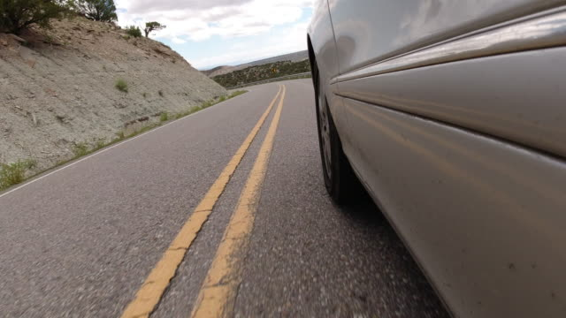 Point of View of from the Side of a Silver Vehicle While Driving down the Colorado National Monument near Grand Junction, Colorado under a Partly Cloudy Sky