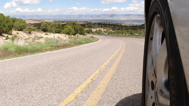 Point of View of from the Side of a Silver Vehicle While Driving down the Colorado National Monument with Fruita and Grand Junction, Colorado in the Background under a Partly Cloudy Sky