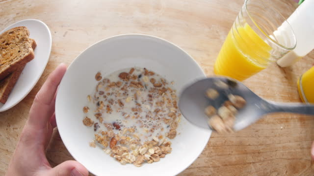 Point of view of man eating cereal and drinking juice