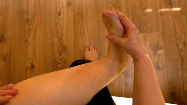 point of view of mature woman rubbing her sore and painful foot and toes doing herself massage therapy - dito del piede video stock e b–roll