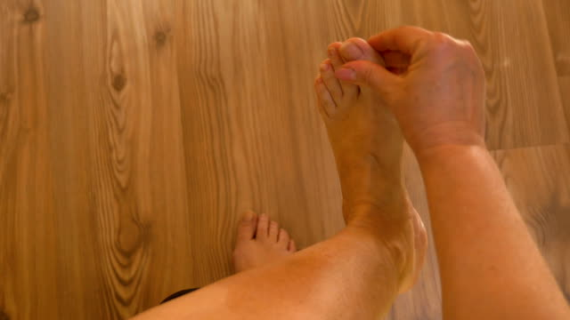Point of view of patient mature woman with rheumatic pains on legs sitting on bed and rubbing her ankle and foot video