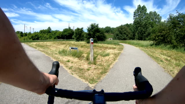 vídeos de stock e filmes b-roll de point of view of reaching forked road on racing bicycle - encruzilhada