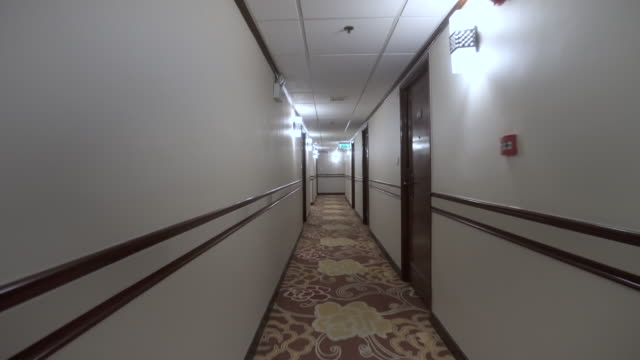 Point of View of Walking Down Old Fashioned Hotel Corridor Passing Through Rooms and Pools of Light